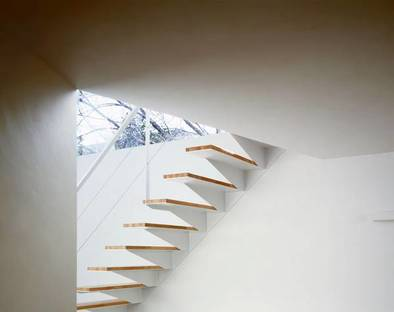 Detail of open staircase painted white with wooden treads