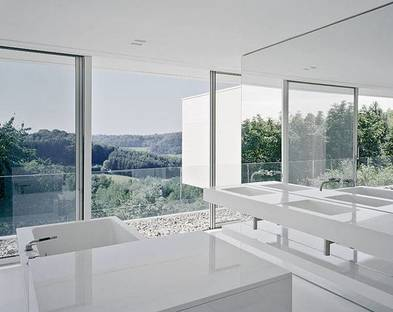 The bathroom with glossy white Corian® elements and wall coverings